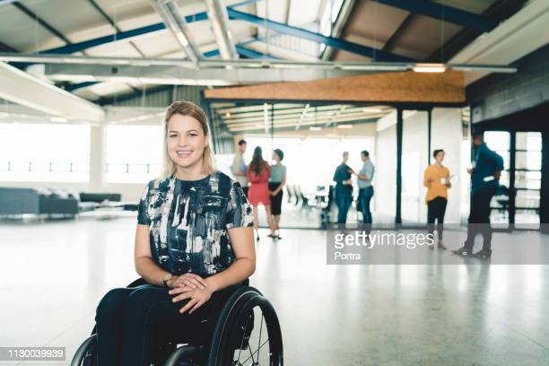 happy businesswoman on wheelchair in creative office - differing abilities female business stock pictures, royalty-free photos & images