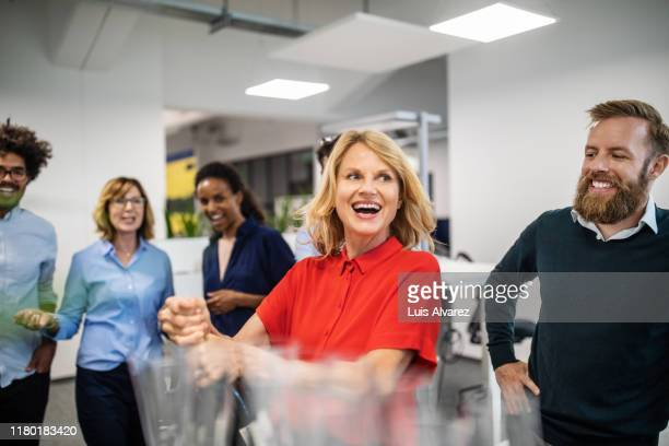 happy businesswoman opening champagne bottle in office - work party stock pictures, royalty-free photos & images
