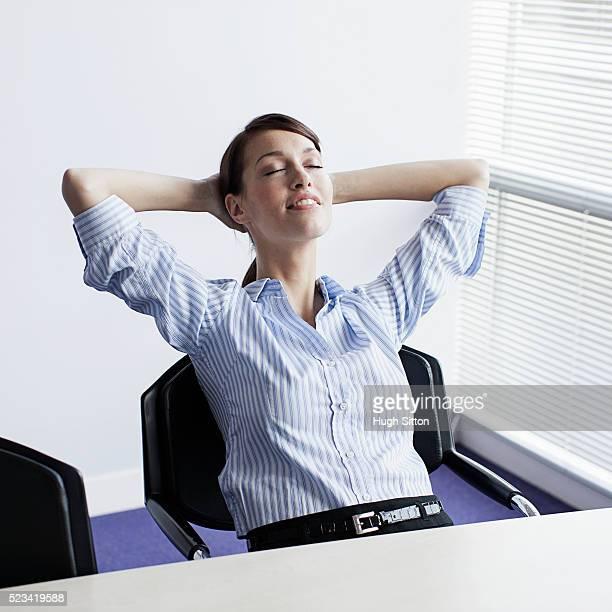 happy businesswoman relaxing in office - hugh sitton stock-fotos und bilder