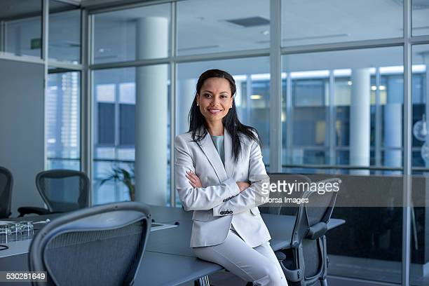 Happy businesswoman sitting arms crossed in office