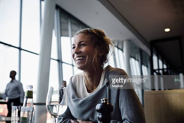 Happy businesswoman sitting at cafe in airport