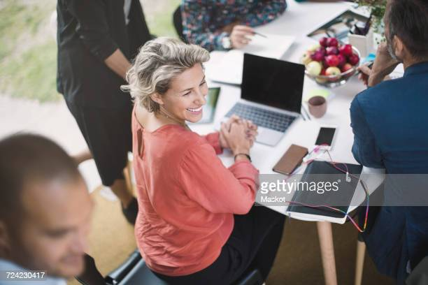 Happy businesswoman sitting at desk with colleagues in portable office truck