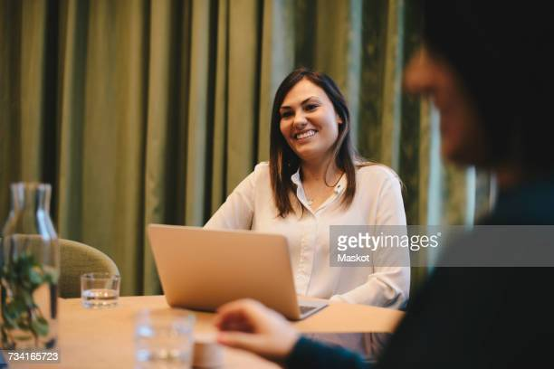 Happy businesswoman sitting wit laptop at conference table in board room