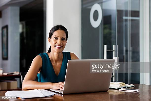 Happy businesswoman sitting with laptop at desk