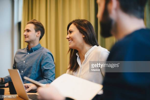 Happy businesswoman sitting with male colleagues in board room meeting