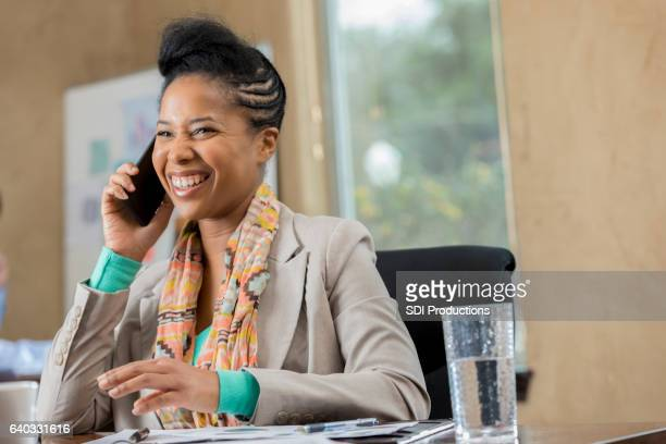 Happy businesswoman smiles while talking with client on the phone
