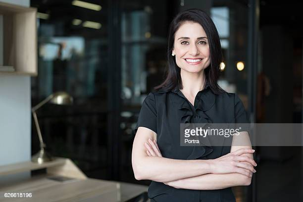 happy businesswoman standing arms crossed - 30 39 years stock pictures, royalty-free photos & images