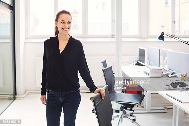 Happy businesswoman standing by chair in office