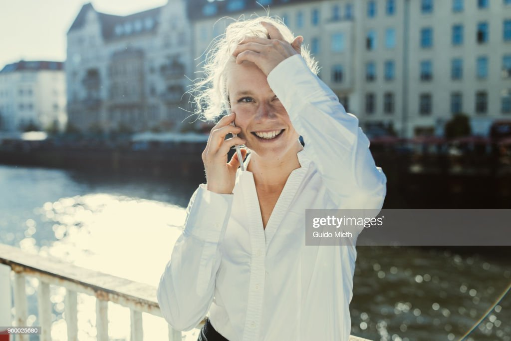 Happy businesswoman standing in front of a river. : Stock-Foto