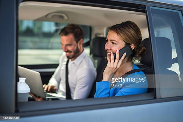 Happy businesswoman talking on cell phone in the car.