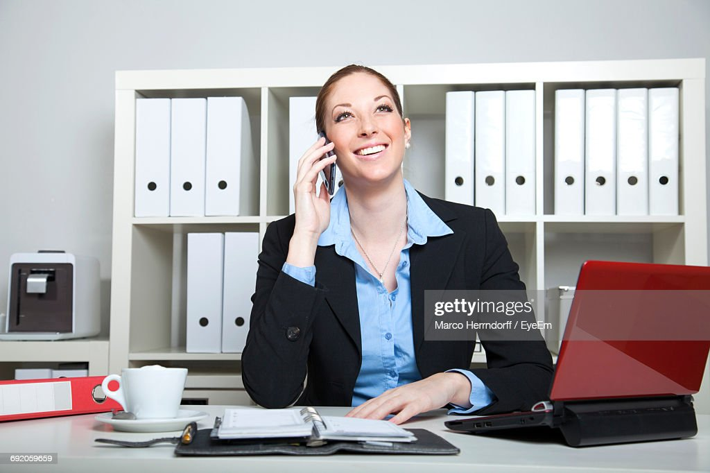 Happy Businesswoman Talking On Mobile Phone While Sitting At