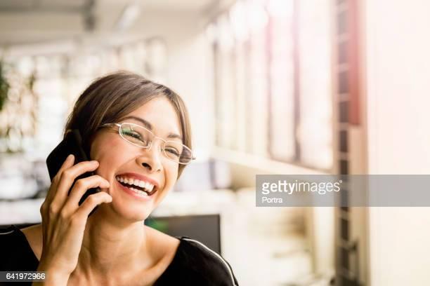 Glücklich Geschäftsfrau telefonieren im Büro