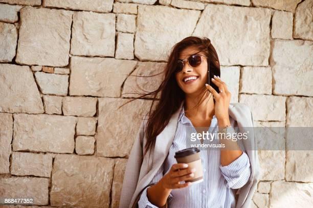 Gelukkig zakenvrouw praten aan de telefoon en het drinken van koffie buitenshuis