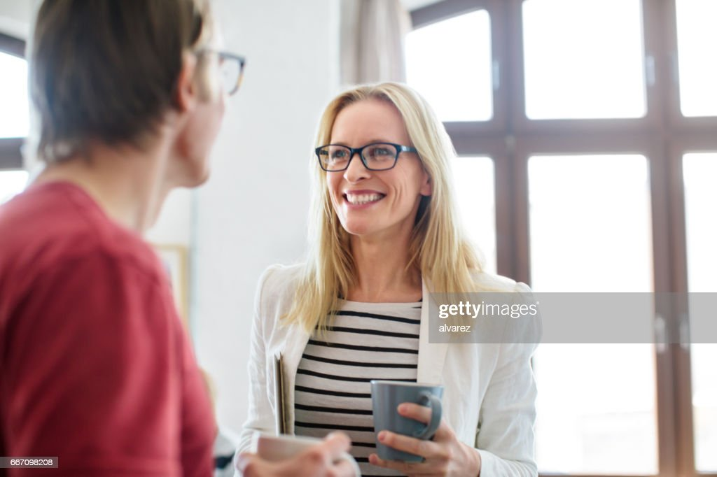 Happy businesswoman talking to colleague in office : Stock Photo
