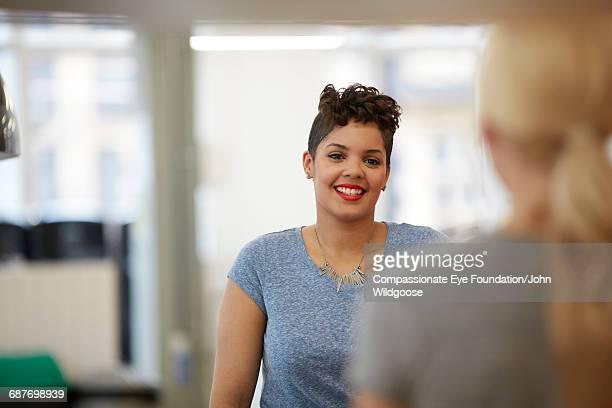 Happy businesswoman talking to coworker in office