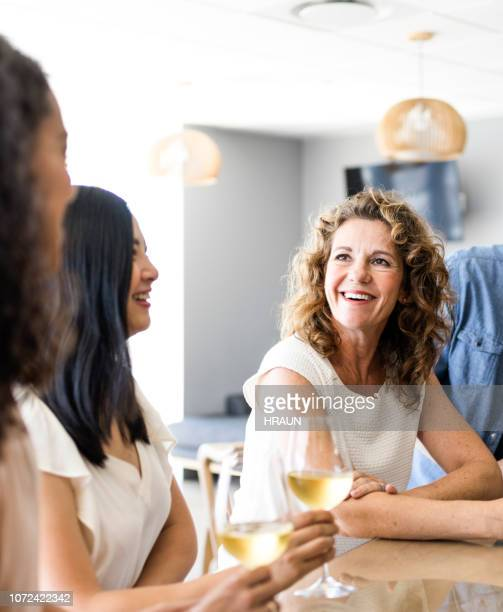 happy businesswoman talking to coworkers in office - table after party stock pictures, royalty-free photos & images