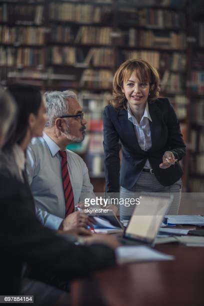 happy businesswoman talking to her colleagues on a meeting in the office. - executive director stock pictures, royalty-free photos & images