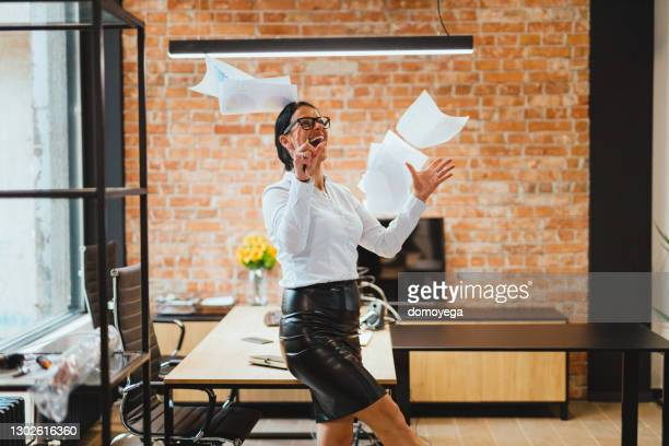 happy businesswoman throwing papers in the air in the office - quitting a job stock pictures, royalty-free photos & images