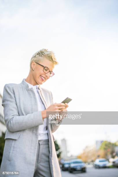 Happy businesswoman typing a message after work.