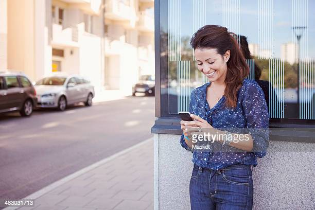 Happy businesswoman using mobile phone against wall by sidewalk