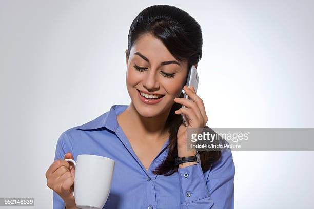 Happy businesswoman using phone while having coffee against gray background
