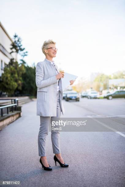 Happy businesswoman waiting for her transportation after work.