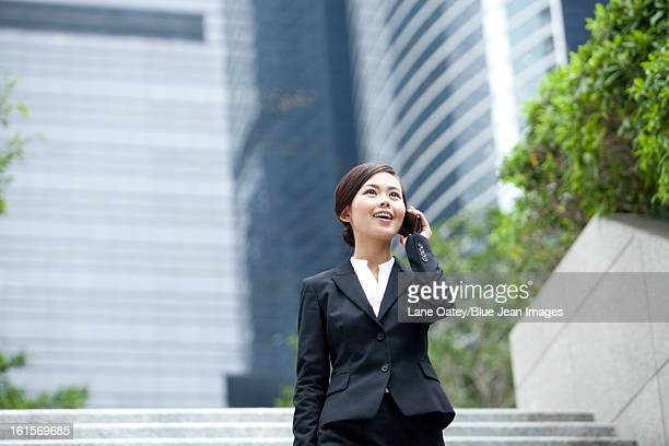 Happy businesswoman walking and talking on the phone outdoors, Hong Kong