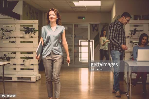 Happy businesswoman walking through office
