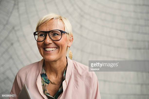 happy businesswoman wearing eyeglasses against wall - 50 54 jahre stock-fotos und bilder