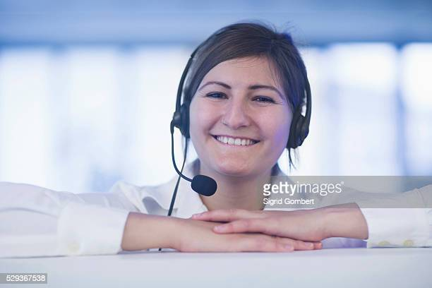 happy businesswoman wearing headset in office, freiburg im breisgau, baden-w��rttemberg, germany - sigrid gombert stock pictures, royalty-free photos & images