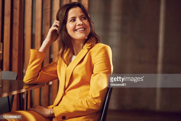 happy businesswoman wearing yellow suit sitting at desk in office - mid adult women stock pictures, royalty-free photos & images