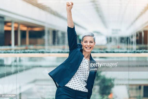 Happy businesswoman with arm raised in triumph