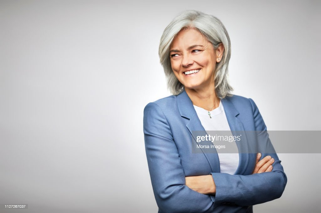 Happy businesswoman with arms crossed looking away : Stock Photo