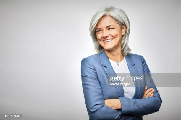 happy businesswoman with arms crossed looking away - cadrage à la taille photos et images de collection