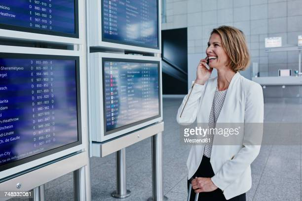 Happy businesswoman with cell phone at timetable at the airport