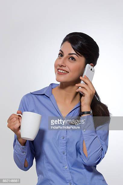 Happy businesswoman with coffee mug using phone over gray background