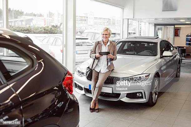 Happy businesswoman with digital tablet looking at car in store