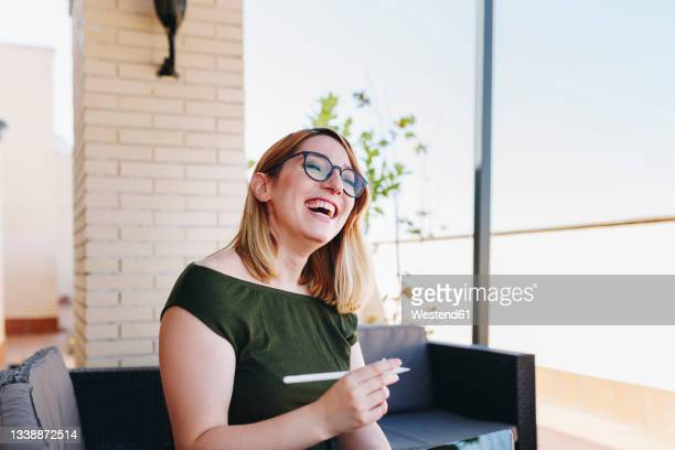 happy businesswoman with digitized pen sitting on sofa at rooftop - one mid adult woman only stock pictures, royalty-free photos & images