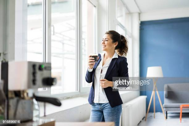 Happy businesswoman with glass of coffee in a loft looking out of window