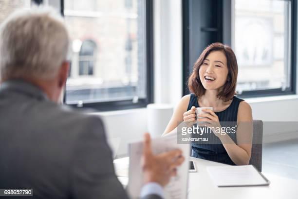 マグカップの同僚を見ていると幸せな実業家 - イギリス ストックフォトと画像