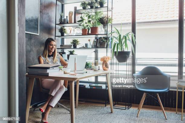 happy businesswoman working on laptop computer while sitting at table in home office - 若い女性だけ ストックフォトと画像