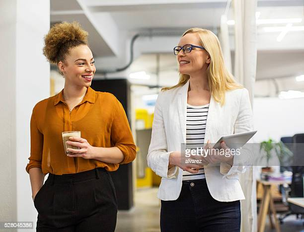 Happy businesswomen communicating in office
