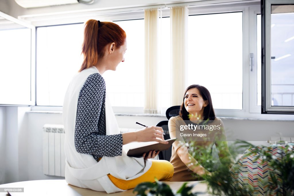 Happy businesswomen discussing in creative office : Stock-Foto