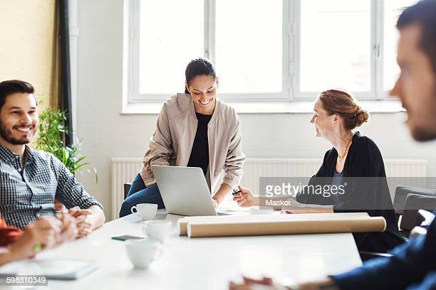 Happy businesswomen discussing over laptop in conference room