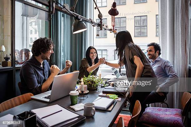 Happy businesswomen holding hands in meeting at creative office