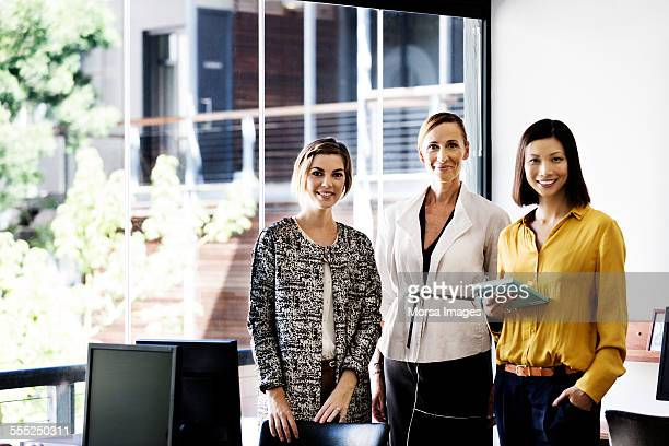 happy businesswomen standing in office - tre persone foto e immagini stock