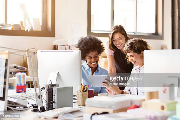 Happy businesswomen using digital tablet in office