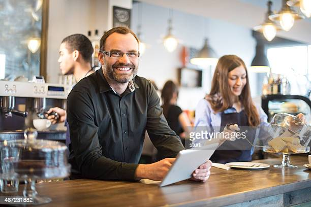 happy cafe owner updating  social media with a digital tablet