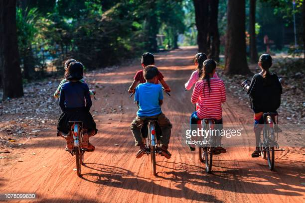 happy cambodian children riding bicycles, cambodia - traditionally cambodian stock pictures, royalty-free photos & images