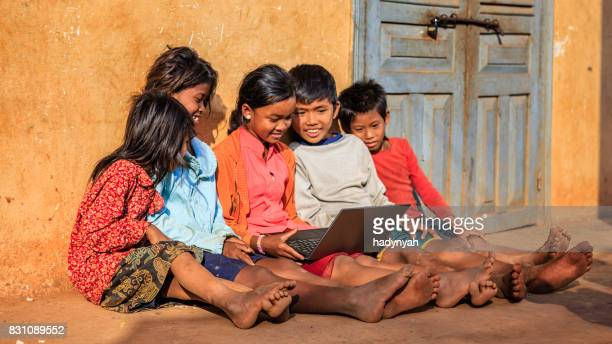 happy cambodian children using laptop on a schoolyard, cambodia - traditionally cambodian stock pictures, royalty-free photos & images